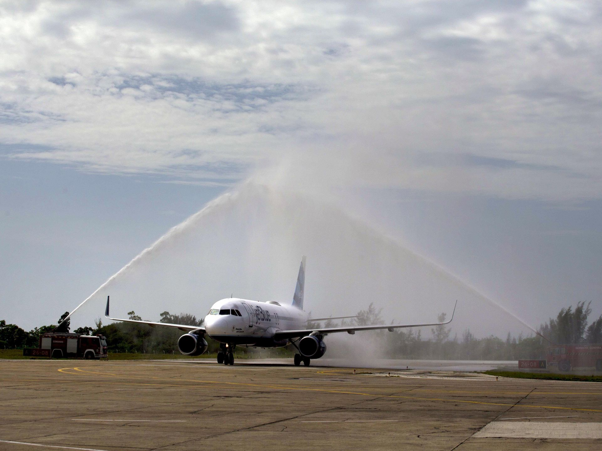 After landing in Santa Clara the JetBlue aeroplane received a ceremonial water canon shower from Cuban fire engines. Photo by USA Today.